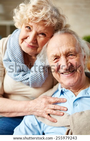 Affectionate seniors looking at camera with smiles