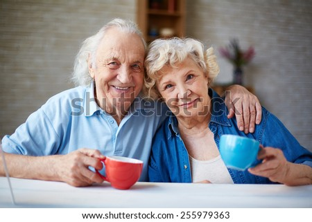 Affectionate seniors with teacups looking at camera