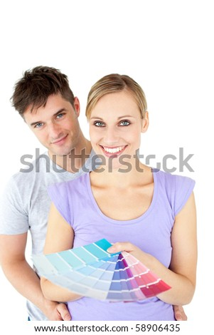 Affectionate young couple choosing colors for painting their room in their new house