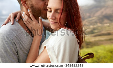 Affectionate young couple embracing each other outdoors. Close up shot of pretty young woman hugging her  boyfriend, enjoying a lovely moment on their vacation. - stock photo