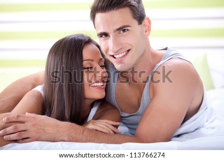 Affectionate young couple in bed - stock photo