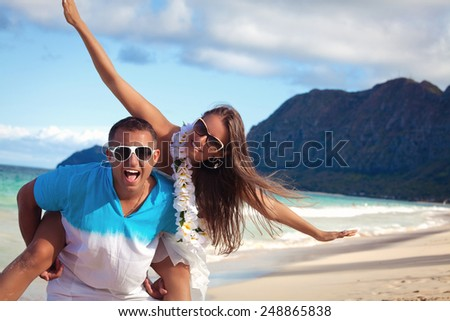 Affectionate young couple on a calm and tranquil beach.  Couple in love, summer luxury vacation in Hawaii. Travel holidays concept. - stock photo
