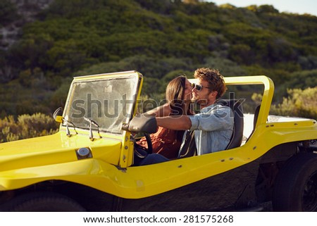 Affectionate young couple on a roadtrip. Man driving car being kissed by his girlfriend. - stock photo