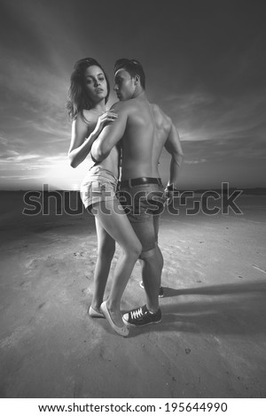 Affectionate young couple posing outdoor at sunset.Wide angle.B&W.