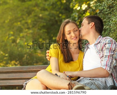Affectionate young couple sitting in park on bench. - stock photo