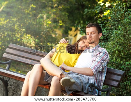 Affectionate young couple sitting in park on bench - stock photo