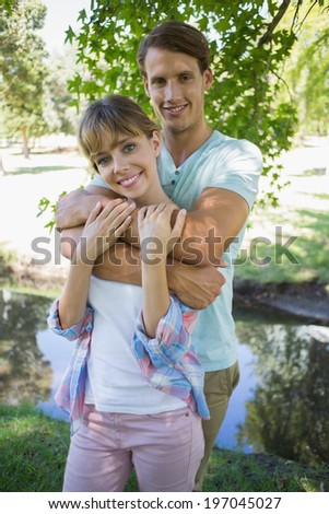 Affectionate young couple standing together in the park smiling at camera on a sunny day