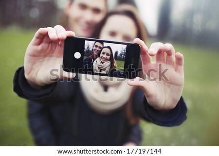 Affectionate young couple taking a self-portrait with a smartphone at the park. Mixed race teenage man and woman outdoors taking their picture with mobile phone. - stock photo