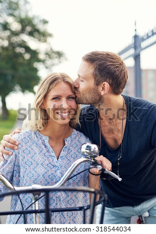 Affectionate young man kissing his girlfriend on the forehead as they enjoy a summer day in the fresh air on their bicycles - stock photo