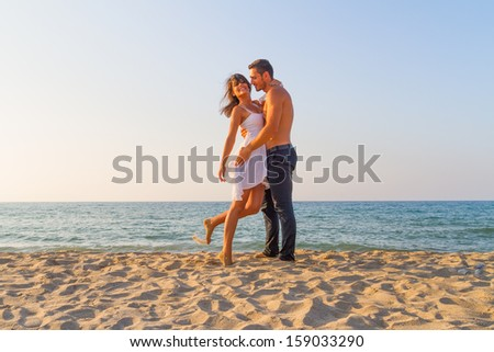 Affectionately embraced, a young couple in love enjoys a mid summer late afternoon on a sandy beach.