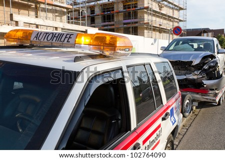 AFFOLTERN, SWITZERLAND-SEPTEMBER 15: Front car crash wreck sits on trailer at roadside to be hauled off by Autohilfe  in Affoltern, SUI on September 15, 2011. - stock photo