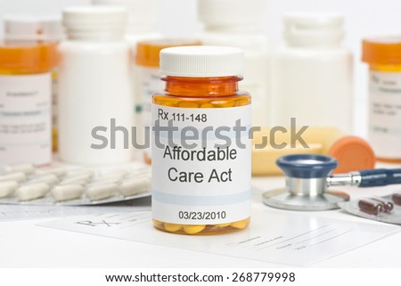 Affordable Care Act pill bottle with prescription and medical supplies.  Labels and all information contained therein are fictitious. - stock photo