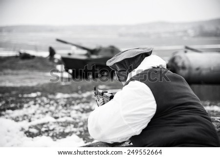 Afghan soldier in action shooting enemy from a rifle. Black and white  - stock photo