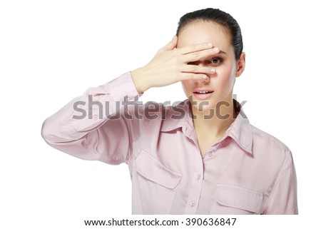 Afraid frightened woman peeking through her fingers. Shy teen girl covering face with hands.