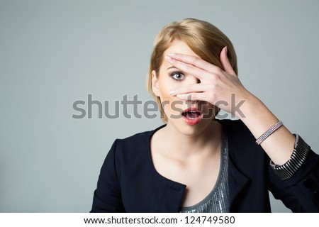 Afraid woman looking between fingers - stock photo