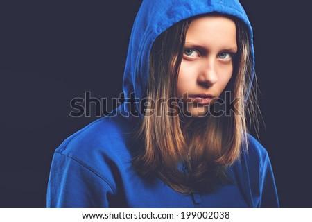Afraided teen girl in hood, studio shot - stock photo