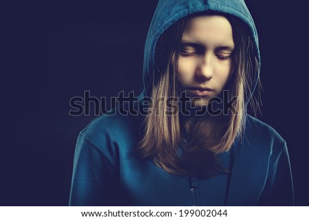 Afraided teen girl in hood, studio shot - stock photo