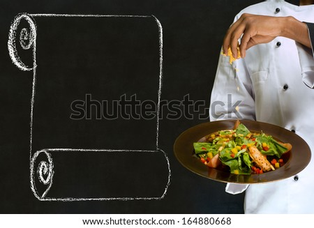 African America chef holding health salad dish with chalk scroll on blackboard Background - stock photo
