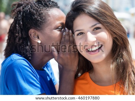 African american and caucasian girlfriend whispering in the city