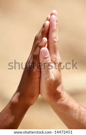 "african american and European american men do a ""high five"" hand clap outside - stock photo"