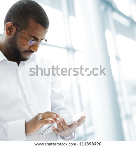 African American Arabic person with pc tablet in modern interior - stock photo
