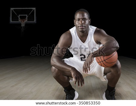 African American basketball Player holding a ball and posing in a darkened basketball arena. - stock photo