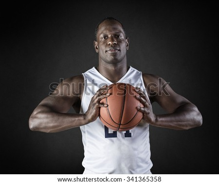 African American Basketball Player portrait holding a ball. Black background - stock photo
