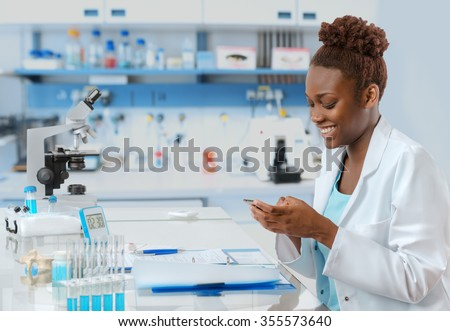 African-american biologist in the lab texting someone on her mobile with a smile - stock photo