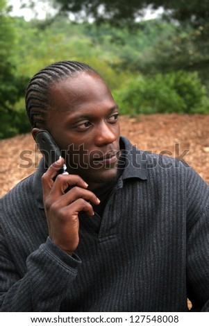 African American Black man outside talking on his cell phone with a thoughtful expression