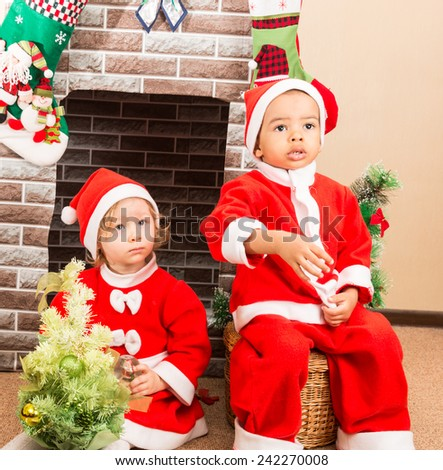 African American boy and girl dressed costume Santa Claus by fireplace. Christmas and New Year - stock photo