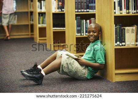 African American boy holding library book - stock photo