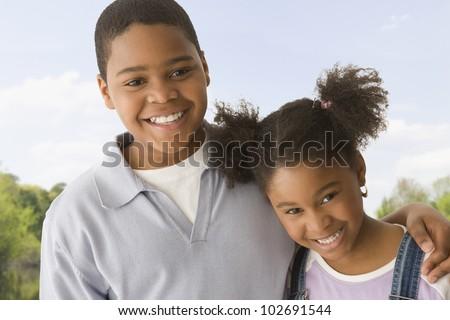 African American brother and sister hugging - stock photo