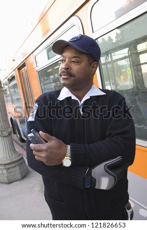 African American bus driver looking away while holding cell phone