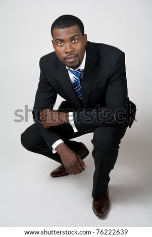 African American business in black suit squatting.