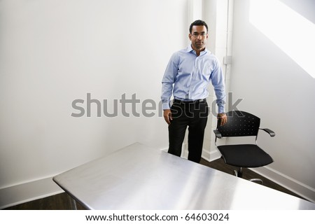 African American business man, 40,  standing in empty office with table and chair - stock photo