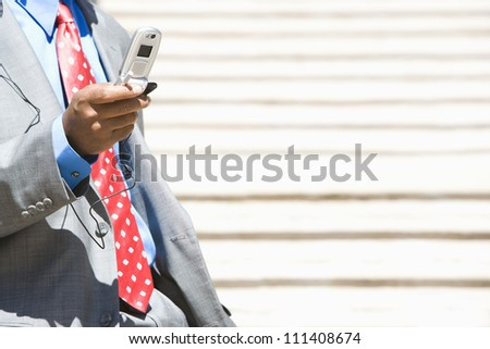 African American business man text messaging through cell phone - stock photo