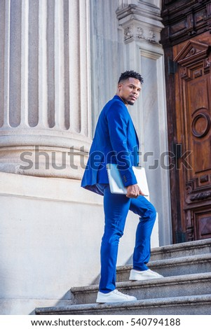 African American Business Man working in New York, wearing blue suit, white sneakers, carrying laptop computer, walking up on stairs into office building, turning back, looking. Color filtered effect