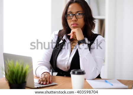 African american business woman is busy with laptop in office while sun shines outdoors - stock photo