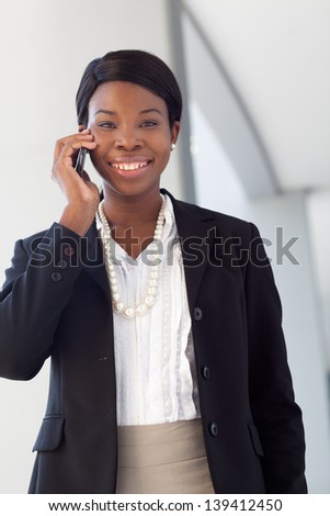 African-american business woman on cell phone, smiling, talking, in suit and pearls outside a modern building.