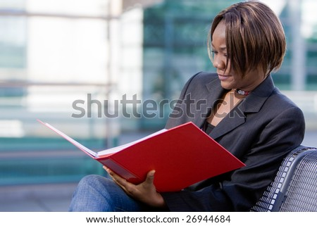 African american business woman reading documents in a folder in front of an office building - stock photo