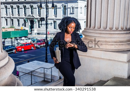 African American Business Woman traveling, working in New York. Holding laptop computer, looking down at wristwatch, a young black lady walking into office building. Filtered look with dark blue tint.