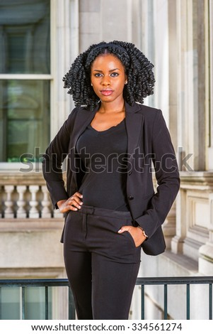 African American Business Woman working in New York. Wearing blazer, v neck undershirt, young pretty black lady with braid hairstyle standing by office building, hand resting on hips, looking at you. - stock photo