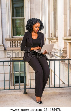 African American Business Woman working in New York. Young black college student with braid hairstyle sitting on railing in vintage style office building, looking down, working on laptop computer.