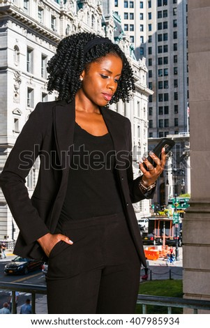 African American Business Woman working in New York. Young black college student with braid hairstyle standing by vintage office building, reading messages on cell phone. Instagram filtered effect.  - stock photo