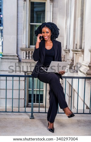 African American Business Woman working in New York. Young black lady with braid hairstyle sitting on railing, smiling, working on laptop computer, making phone call. Filtered look with dark blue tint - stock photo