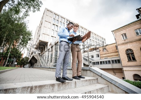 African American businessman and a Caucasian businessman discussing and looking at the documents on city background, bottom view