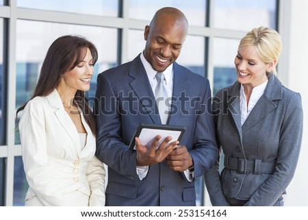 African American businessman and two businesswomen, business man, business woman, using tablet computer