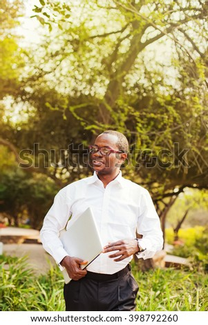 african american businessman carrying laptop walking in a park - stock photo