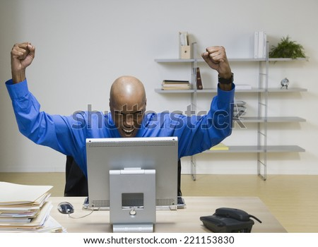 African American businessman cheering at desk - stock photo