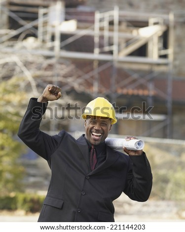 African American businessman cheering with blueprints